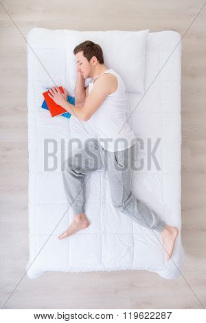 Sleeping man lying in bed with book