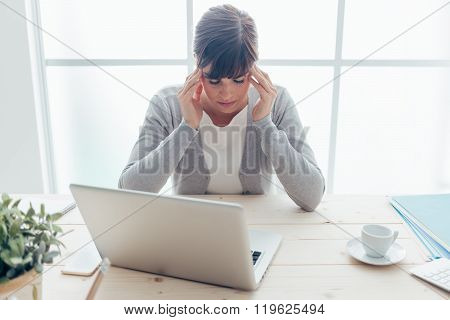 Exhausted young woman working at office desk touching her temples she is having a bad headache stressful life and illness concept poster