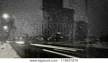 night view of the street through the glass with raindrops