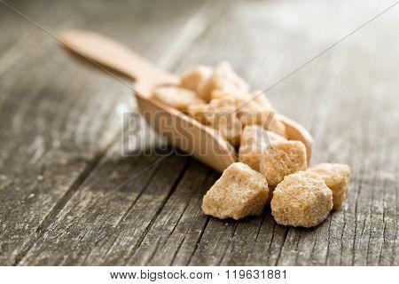 unrefined cane sugar in wooden scoop