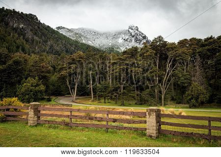 wood fence in the park with big snow mountains, bariloche, patagonia, argentina, south america