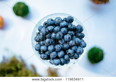 A Few Blueberries In Glass Vase On White Background