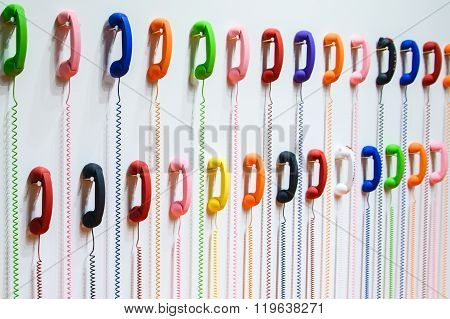 Two Rows Of Colorful Handsets Are Hanging On A White Wall. Wires Hanging Down