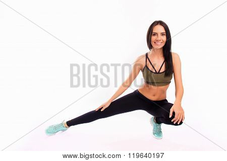Young Fit Smiling Sportswoman Stretching On White Background