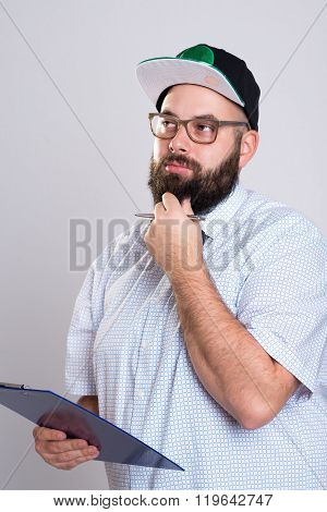 young bearded man with clipboard and baseball cap poster