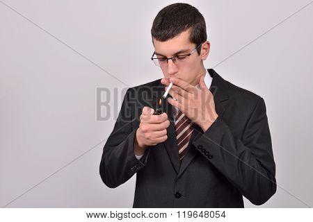 Young Man Dressed In Tuxedo Lighting Cigarette In Studio