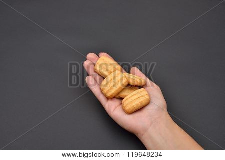 Hand Of A Woman Holding A Pile Of Crackers Isolated On Black Background. Spice. Taste. Cooking. Food