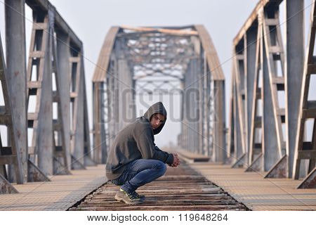 Thinker Sad Teenager In Depression Sitting Crouched On The Bridge At The Sunset And Looking True Cam