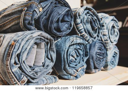 background of a stack rolled jeans on shelf