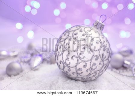 Christmas ball  in the snow on abstract background