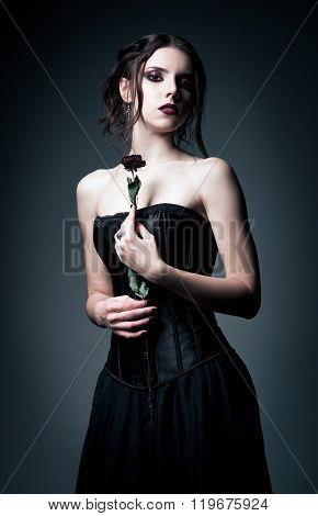 Portrait Of Beautiful Goth Girl Holding Withered Flower In Hands