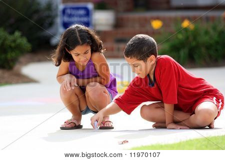 Girl and boy in their driveway playing with chalk