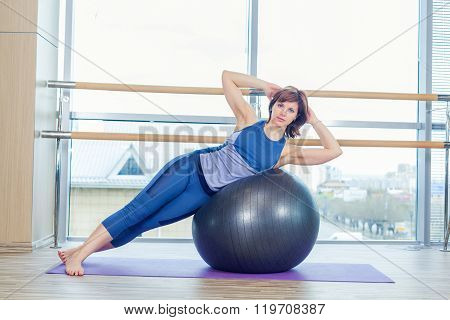 Young and athletic girl using fitness ball in a gym.
