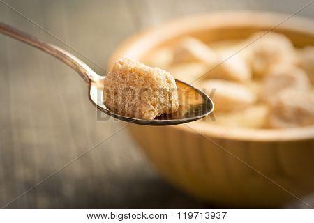 unrefined cane sugar in silver spoon