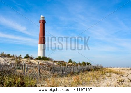 "a lighthouse on the beach. there is also an old wooden fence on the beach in this landscape. this is barnegat lighthouse nicknamed ""old barney"" at long beach island new jersey. poster"