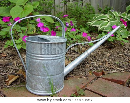 An old tin watering can on a brick patio in a flower garden.