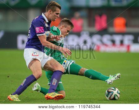 VIENNA, AUSTRIA - NOVEMBER 9, 2014: Alexander Gruenwald (#10 Austria) and Domink Starkl (#34 Rapid) fight for the ball in an Austrian soccer league game.