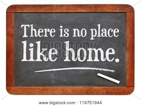 There is no place like home proverb white chalk text on a vintage slate blackboard