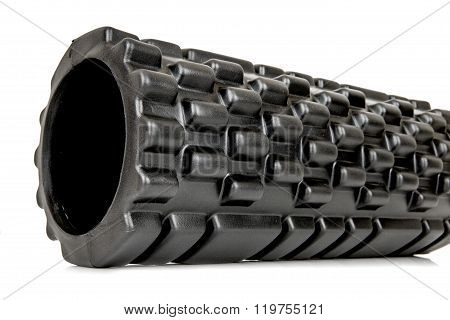 A black bumpy foam massage roller. Foam rolling is a self-myofascial release technique that is used by athletes and physical therapists to inhibit overactive muscles. poster