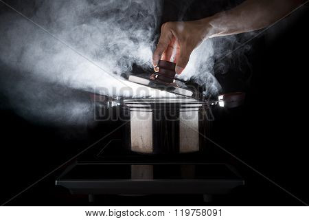 Hand Of Chef Open Hot Stream Pot With Beautiful Studio Lighting Against Black Background Use For Peo