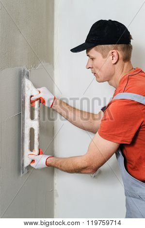The Worker Puts The Stucco On The Wall