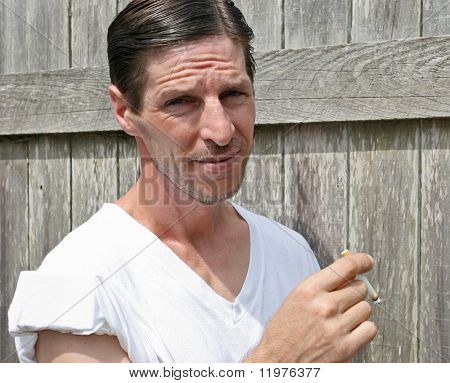 A rough looking man smoking a cigarette against a fence.