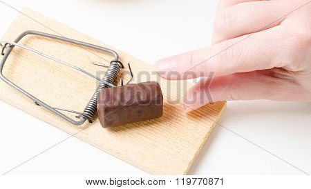 hand and diet mousetrap with chocolate candy on white