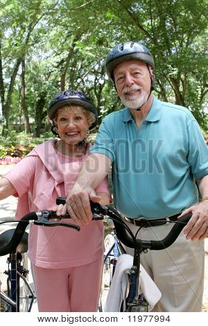 An attractive senior couple bicycling with helmets on.