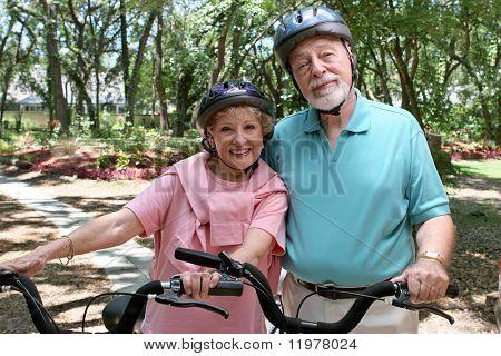 Een aantrekkelijke hoge paar fietsen samen dragen helmen.