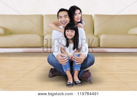 Little Girl Sitting On The Floor With Her Parents