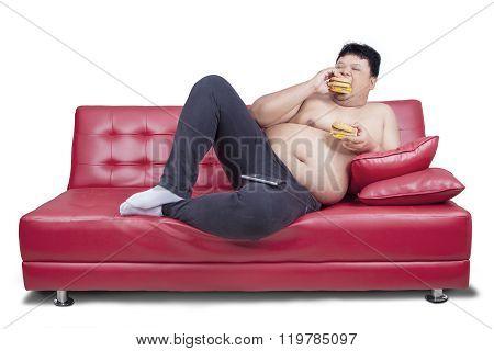 Obese Man Eats Two Hamburger On Sofa