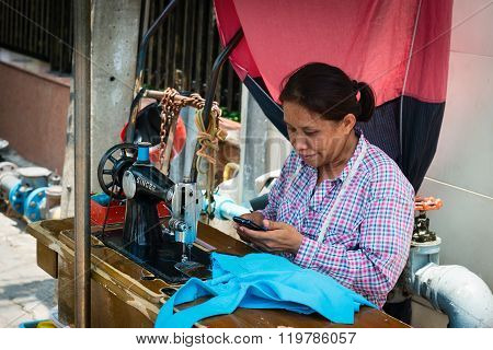 Street Seamstress With Old Sewing Machine On Wooden Bench