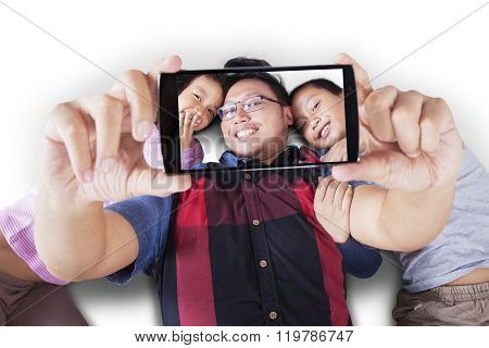 Two Kids And Father Taking Selfie Together