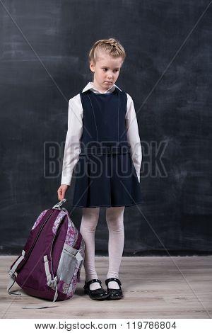 Latecomers little schoolgirl with backpack near blackboard poster
