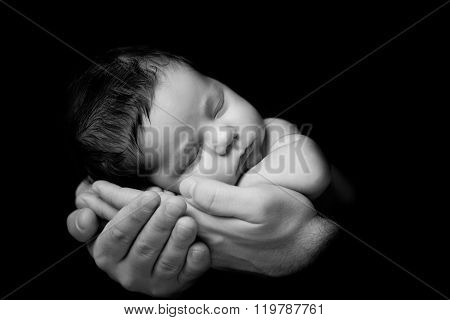 Father's Love. Little Newborn Baby Sleeping In Dad 's Hands. Close-up On A Black Background