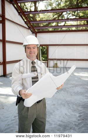 A construction inspector on the job site holding blueprints and smiling.