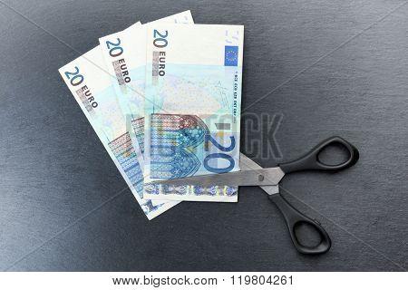 Concept of spending money - scissors cut money on black background