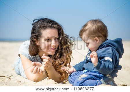 Beautiful young mother with little son lying on the sand at the beach in spring.