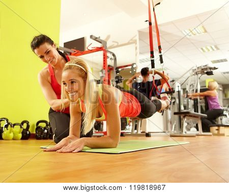 Young sporty woman training in gym with personal trainer.