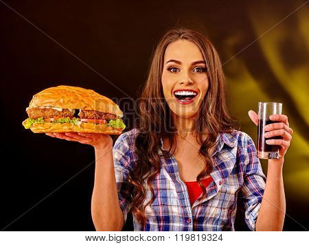 Girl keeps big hamburger and drink. Fastfood concept. Cheeseburger on foreground.