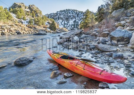 whitewater kayak with a paddle on a river shore  - Arkansas River, Colorado in winter scenery