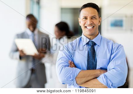 good looking corporate worker in modern office with colleagues on background