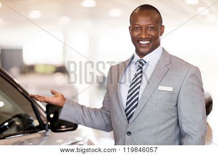 friendly african car dealer presenting new vehicle in showroom