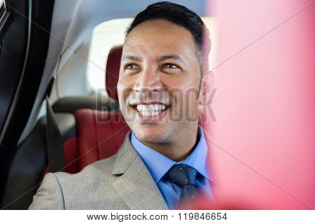 handsome middle aged businessman sitting on the backseat in a car
