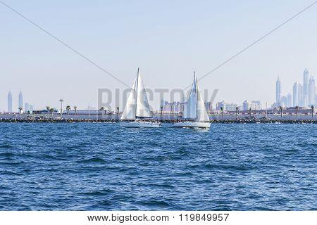background seascape two sailboat met opposite the Dubai Marina