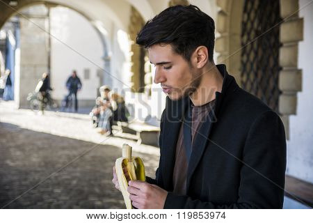 Man with banana standing on street in Lausanne while looking down