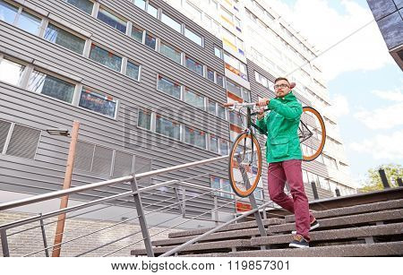 people, sport, style, leisure and lifestyle - young hipster man carrying fixed gear bike on shoulder down stairs in city