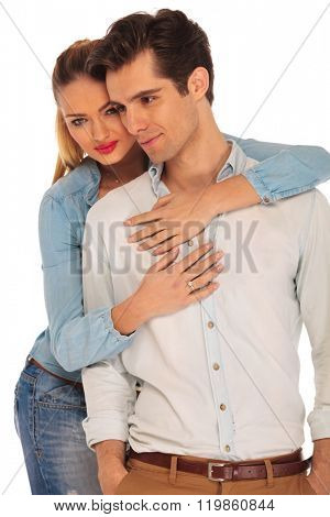 attractive man posing with both hands in pockets while his girfriend is holding him from behind in isolated studio background
