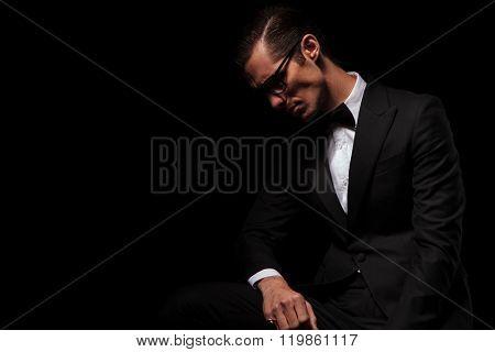 portrait of classy man in black tux wearing glasses posing in dark studio background looking down