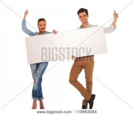 attractive couple posing with legs crossed in isolated studio background while holding white blank sign and showing the victory sign